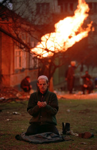 Man praying in Chechnya in front of flaming gas pipe, c.1995