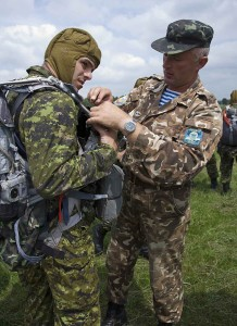 Ukrainian airborne officer checks Canadian parachute kit before exercise